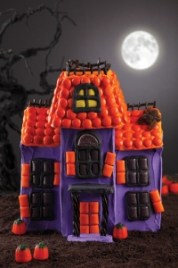 A haunted gingerbread mansion decorated in black, orange, and purple candy